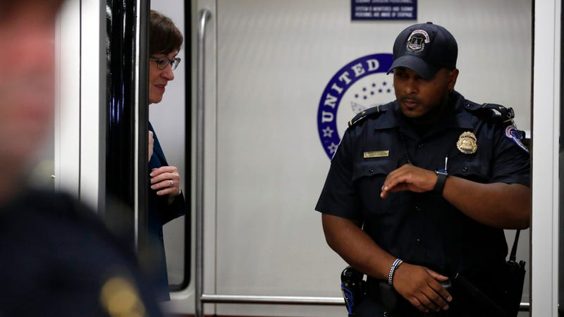 Sen. Susan Collins, R-Maine, stands in a Senate subway car with a Capitol Hill Police officer, on Capitol Hill, Wednesday, Oct. 3, 2018 in Washington.