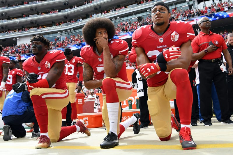 Eli Harold #58, Colin Kaepernick #7 and Eric Reid #35 of the San Francisco 49ers kneel on the sideline during the anthem prior to the game against the Dallas Cowboys at Levi's Stadium on October 2, 2016 in Santa Clara, California.