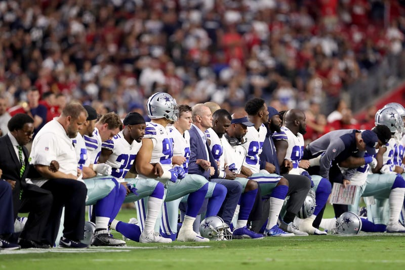 Members of the Dallas Cowboys link arms and kneel during the national anthem before the start of the NFL game against the Arizona Cardinals at the University of Phoenix Stadium on Sept. 25, 2017, in Glendale, Ariz. (Christian Petersen/Getty Images)