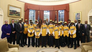 President Barack Obama and first lady Michelle Obama pose with the Jackie Robinson West All Stars Little Baseball League in the Oval Office of the White House in Washington, D.C., Nov. 6, 2014. YURI GRIPAS/AFP/Getty Images