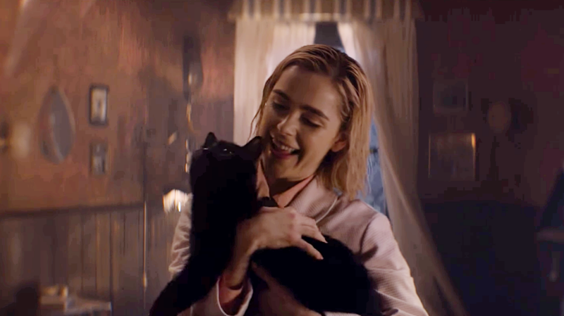 Sabrina (Kiernan Shipka) meets her new feline friend.