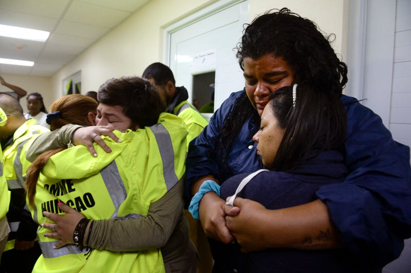 Rescue-team members Candida Lozada and Stephanie Rivera, along with Mary Rodriguez and Zuly Ruiz, embrace as they wait to assist in the aftermath of Hurricane Maria in Humacao, Puerto Rico, on Sept. 20, 2017. (Carlos Giusti/AP Images)