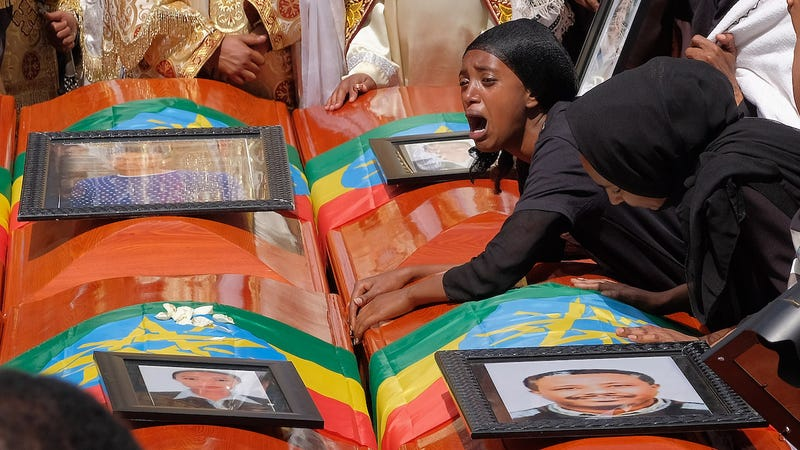 A woman lays on the coffin of her loved one during a memorial service for the Ethiopian passengers and crew who died on Flight 302