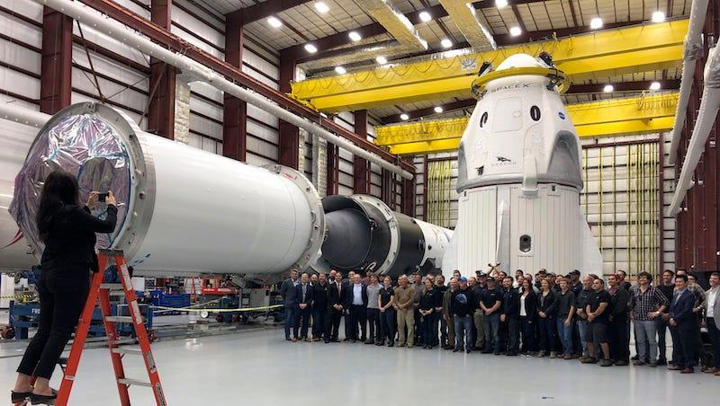 Los empleados de SpaceX posan para una foto en frente de la cápsula Dragón. Están trabajando en la cápsula para mandar a astronautas a la Estación Espacial Internacional.