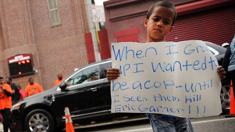 A child holds up a sign outside the Bethel Baptist Church before the funeral for Eric Garner on July 23, 2014, in New York City.