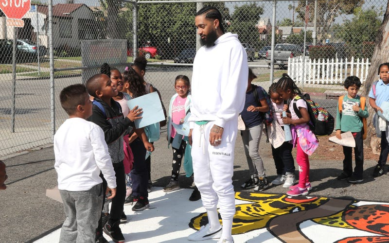 Nipsey Hussle greets kids at the Nipsey Hussle x PUMA Hoops Basketball Court Refurbishment Reveal Event on October 22, 2018 in Los Angeles, California.