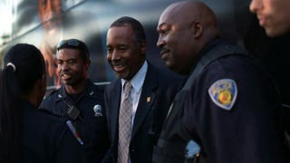 Ben Carson (center) speaks with police officers as he prepares to board his bus after a stop to sign his book at a Barnes and Noble store in Fort Lauderdale, Fla., Nov. 5, 2015. Carson is leading the field in some of the recent polling for the Republican presidential-nomination contest.Joe Raedle/Getty Images
