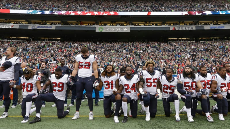Houston Texans players kneel and stand during the singing of the national anthem before an NFL football game against the Seattle Seahawks on Oct. 29, 2017, in Seattle. (Elaine Thompson/AP Images)