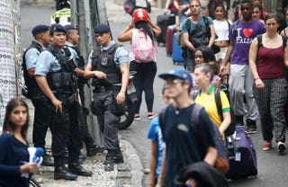 Police keep watch as tourists carry their luggage to a tour bus near the pacified Pavao-Pavaozinho community, just blocks from Copacabana Beach, on April 23, 2014, in Rio de Janeiro, Brazil.Mario Tama/Getty Images
