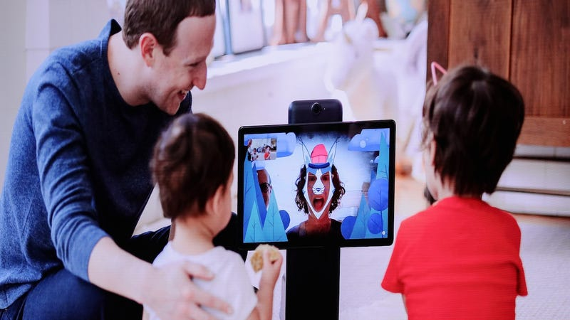Facebook CEO Mark Zuckerberg shows unnamed kids one of the social media giant's latest in-home spy devices