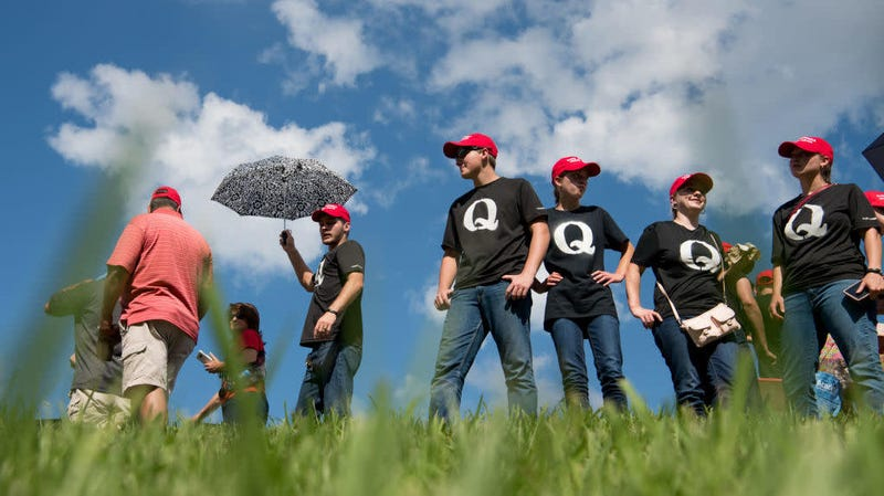 "Supporters of Donald Trump wearing ""QAnon"" T-shirts wait in line before an October 2018 campaign rally in Tennessee. Danielle Stella, a reported supporter of the debunked far-right conspiracy theory and also a GOP candidate for Ilhan Omar's House seat, is facing some far-out troubles of her own."