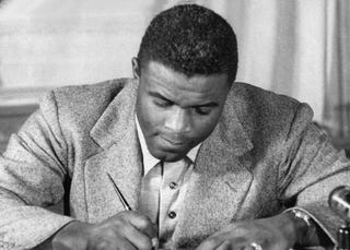 Jackie Robinson signs contract to play for the Brooklyn Dodgers. (Getty)