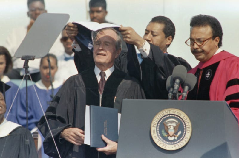President George Bush, left, is bestowed the ceremonial mantle of an honorary doctor of law degree from Hampton University by the chairman of the board of trustees, Ray LeFlore, center, as the school's president, Dr. William Harvey, looks on during commencement exercises in Hampton, Va., May 13, 1991. Bush delivered the commencement address. (AP Photo/Steve Helber)