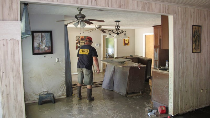 62-year-old Highlands resident Dwight Chandler, who lives near the flooded Highlands Acid Pit, examines his flood-damaged home. Photo: AP
