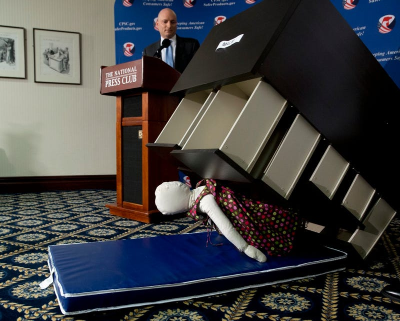 Consumer Product Safety Commission (CPSC) Chairman Elliot Kaye watches a demonstration of a child dummy being crushed at a news conference Tuesday (Associated Press)