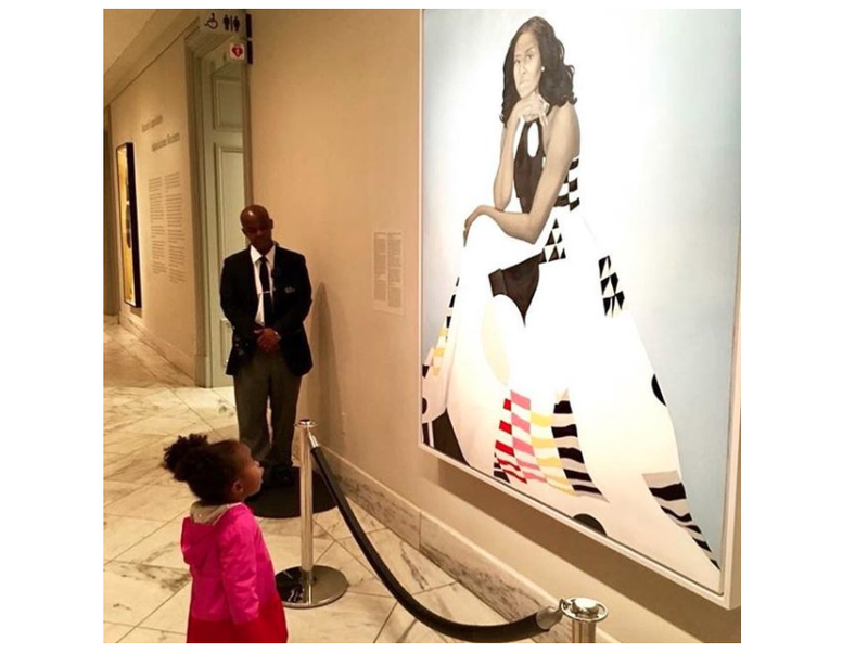 Two-year-old Parker Curry gazes at a portrait of former first lady Michelle Obama at the National Portrait Gallery in Washington, D.C.