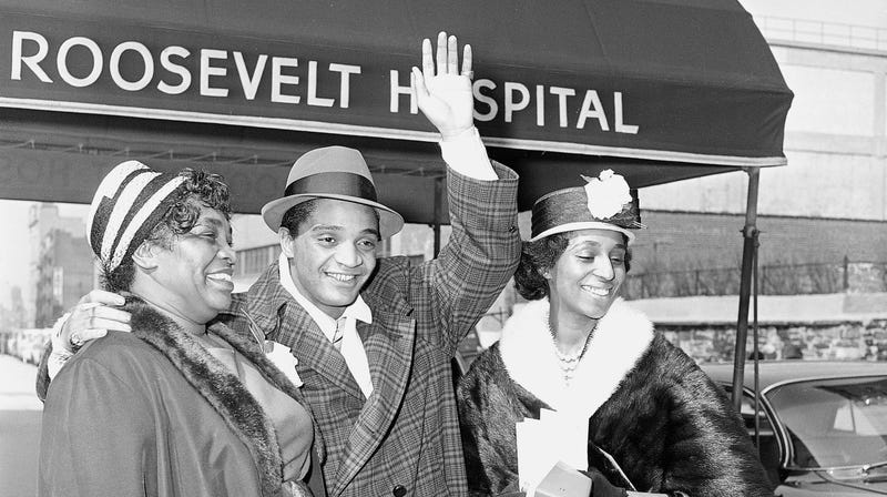 Rock and Roll singer Jackie Wilson waves as he leaves New York's Roosevelt Hospital with his mother Elizabeth Lee, left, and his then-wife Friea Wilson on March 18, 1961.