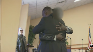 Pastor Larry Wright hugs the unidentified man as he returned to ask for forgiveness.WRAL Screenshot