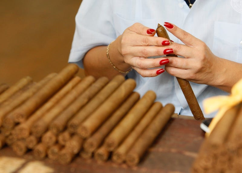 A worker applies an outer wrapper to a cigar at a cigar factory in Miami's Little Havana neighborhood in 2009 (AP Photo/Wilfredo Lee)