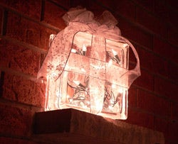 the househacker blog posts instructions on how to feed christmas lights into a glass block for a festive glowy diy holiday decoration