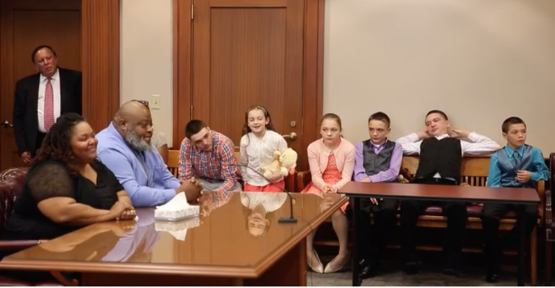 Christina and Christopher Sanders (far left) with their six adopted children (Cincinnati Enquirer screenshot)