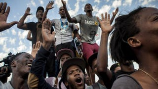 "Students in Cape Town, South Africa, cheer after the statue of British colonialist Cecil Rhodes is removed from the University of Cape Town April 9, 2015. The statue was removed as a result of a monthlong protest by students saying the statue glorified someone ""who exploited black labor and stole land from indigenous people.""  Charlie Shoemaker/Getty Images"