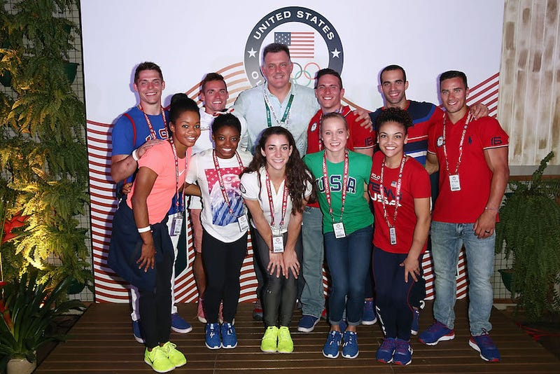 Steve Penny poses with members of the US Olympics gymnastics team (photo via Getty Images)