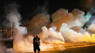 Demonstrators, protesting the shooting death of teenager Michael Brown, flee as police shoot tear gas into the crowd of several hundred after someone reportedly threw a bottle at the line of police Aug. 13, 2014, in Ferguson, Mo.Scott Olson/Getty Images
