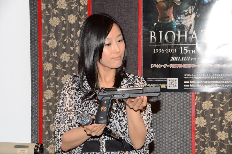 Illustration for article titled A Lady Holds a Resident Evil Pistol. Capcom Copyrights a Cake.
