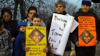 Protesters display sigs at Cudell Commons Park in Cleveland, Ohio, November 24, 2014 during a rally for Tamir Rice, a 12-year-old boy shot by police on November 23. JORDAN GONZALEZ/AFP/Getty Images