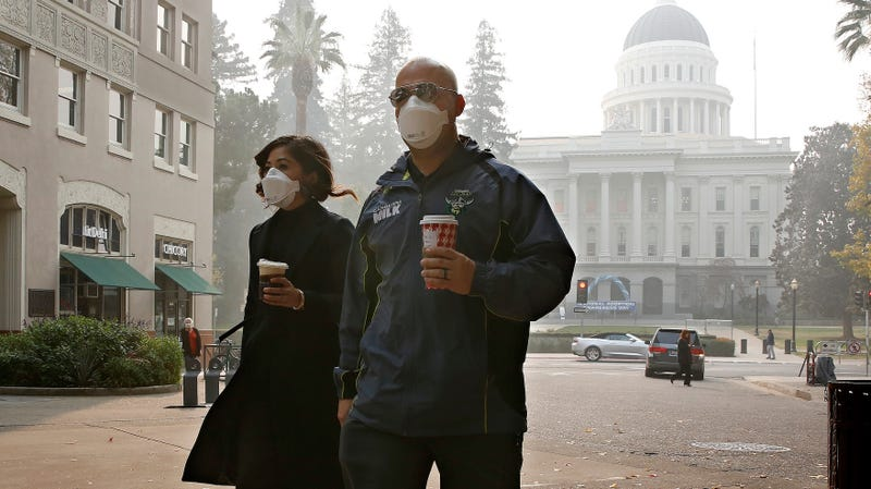 Two people don masks to deal with the smoke from the Camp Fire that shrouds the state Capitol in Sacramento, California.