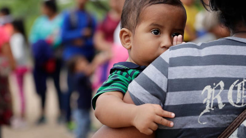 In this March 14, 2019 photo, a 7-month old boy peers over the shoulder of his mother as they wait for DHS agents to apprehend them at the U.S.-Mexico border near McAllen, Texas.