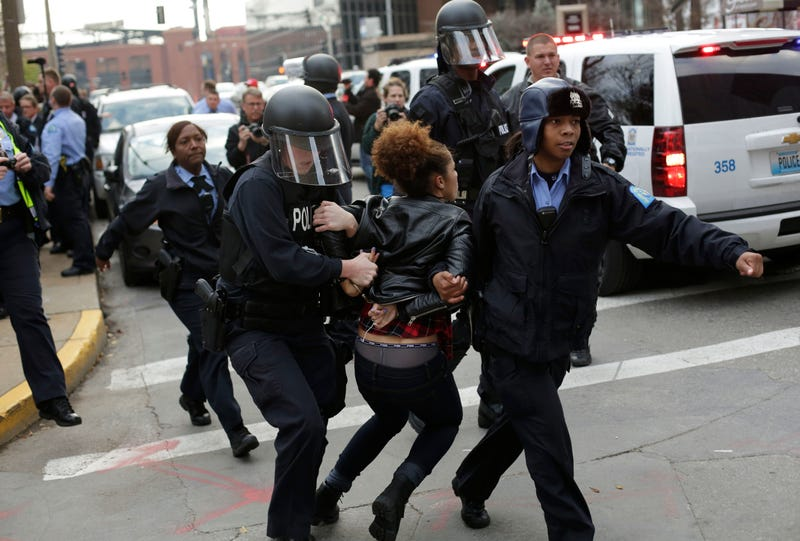 A demonstrator protesting the shooting death of Michael Brown is arrested by police officers in riot gear Nov. 30, 2014, in St. Louis, Mo.