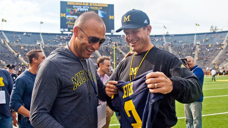 Derek Jeter and Jim Harbaugh presumably discuss fashion in September, 2015. Photo credit: Tony Ling/AP