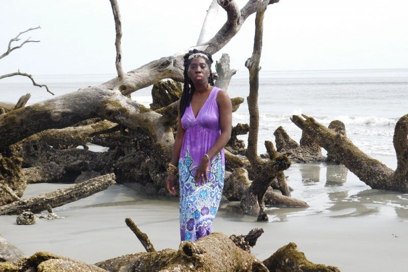 Queen Quet stands among damaged trees on Hunting Island, S.C.