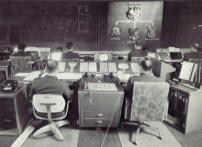 Original caption from 1970: AIR DEFENSE WATCH - These display screens would display signs of air attack against Canada and the United States. By pushing buttons, the NORAD battle staff members can take an electronic look at the tracks of space satellites or aircraft, which are chartered on the display by computers This is the nerve center which would give the first warning of attack, and the command post from which NORAD battle commanders would direct the defensive air battle. (Photo scanned by Memory Hole 2 from the book NORAD Command Post: The City Inside Cheyenne Mountain by Henry W. Hough)