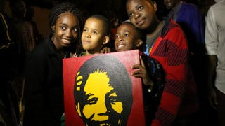 South Africans hold pictures of former South African President Nelson Mandela as they pay tribute following his death in Johannesburg, Dec. 6, 2013.ALEXANDER JOE/AFP/Getty Images