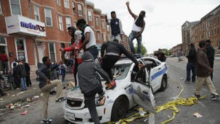 Demonstrators climb on a destroyed Baltimore police car in the street near the corner of Pennsylvania and North avenues during protests following the funeral of Freddie Gray April 27, 2015, in Baltimore.Chip Somodevilla/Getty Images
