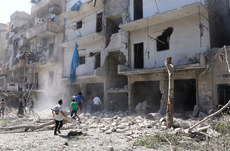 Photo via Getty: Search and rescue team members inspect the debris of buildings after Russian army aircrafts hit residential areas at Sukkari district of Aleppo, Syria on September 07, 2016.