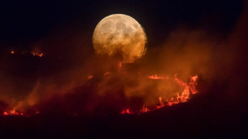 The full moon rises over the Saddleworth Moor fire.