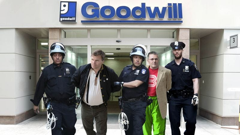 Goodwill executives are led from the company's headquarters, where authorities reportedly found file cabinets filled with hundreds of Super Nintendo cartridges and needlepoint Christmas stockings.