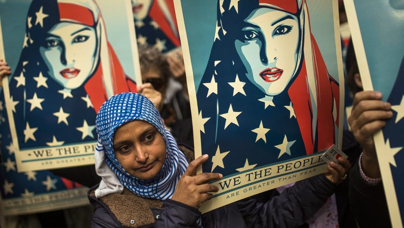 People carry posters during a rally against Trump's original executive order banning travel from seven Muslim-majority nations, in New York's Times Square, Sunday, Feb. 19, 2017. Photo via AP