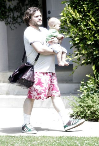 Illustration for article titled Jack Black's Charming Combination Of Hawaiian-Print Shorts, Scruffy Beard, Infant Son And Eggplant-Colored Man-Bag