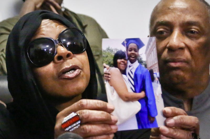 """Carol Gray holds a photo of her son, Kimani """"Kiki"""" Gray, with the aid of New York City Councilman Charles Barron, during a news conference in New York on March 13, 2013. (Bebeto Matthews, File/AP Images)"""
