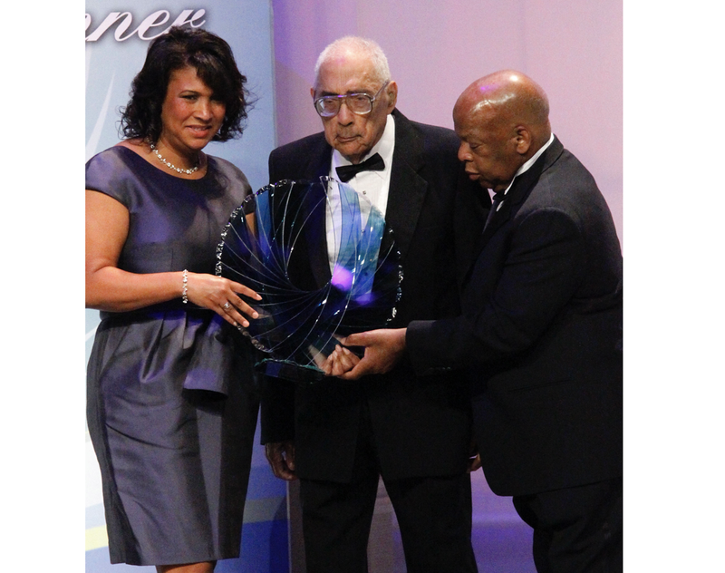 Journalist Simeon Booker (center) is presented with a Phoenix Award at the Congressional Black Caucus Foundation's annual Legislative Conference Phoenix Awards Dinner in Washington, D.C., on Sept. 18, 2010. (Ann Heisenfelt/AP Images)