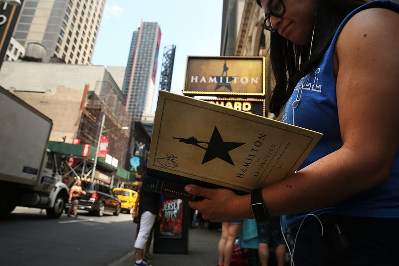 A woman displays her Hamilton autograph book outside the popular Broadway show Hamilton on June 21, 2016, in New York City. Spencer Platt/Getty Images