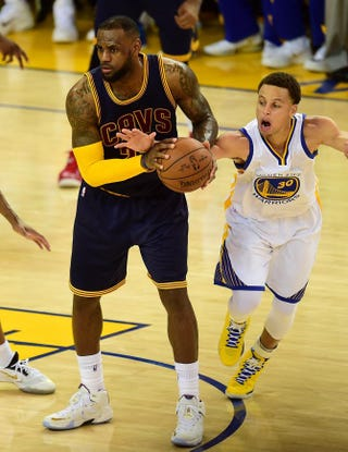 Stephen Curry of the Golden State Warriors (right) strips the ball from LeBron James of the Cleveland Cavaliers during overtime in Game 1 of the 2015 NBA Finals in Oakland, Calif. The Warriors defeated the Cavaliers 108-100 in overtime.FREDERIC J. BROWN/AFP/Getty Images