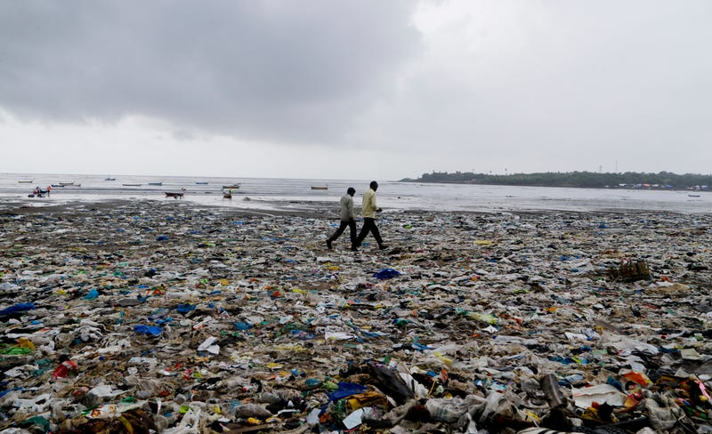 In this Aug. 19, 2017 photo, people walk past plastic bags and garbage  on the Arabian Sea coast in Mumbai, India. Photo: AP