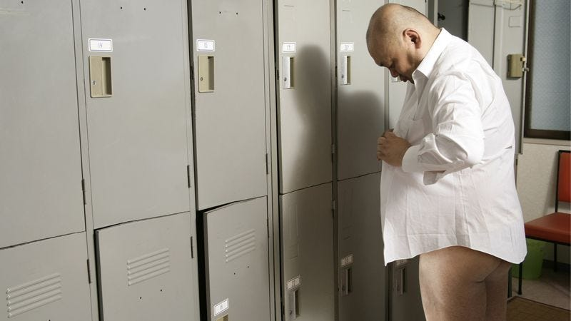 Middle aged man in gym locker room puts shirt on before underwear