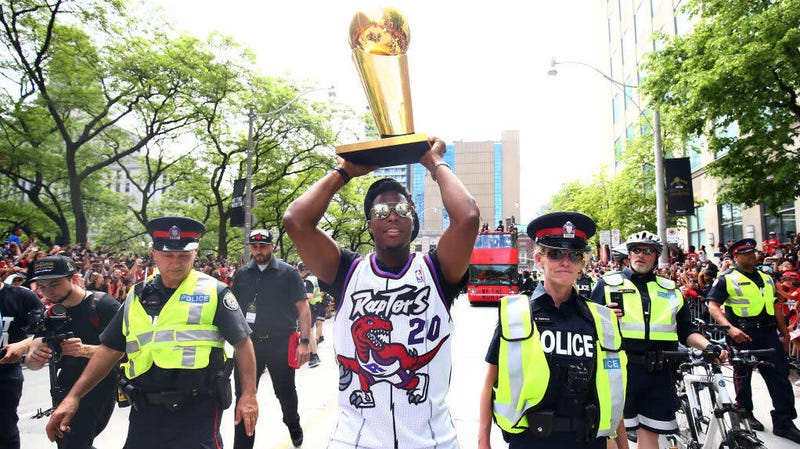 Kyle Lowry of the Toronto Raptors walks down the street with the NBA Championship trophy during the Toronto Raptors victory parade on June 17, 2019, in Toronto. Some 1 million people turned out for the celebration, which was marred when gunshots rang out leaving four people hurt. Police arrested three.